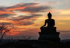 在日落天空背景的菩萨雕象在泰国 库存图片