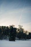 在日落天空,在前景的冬天场面的飞机轨道 库存图片