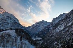在日落天空,朱利安阿尔卑斯,斯洛文尼亚的田园诗高山多雪的山景 库存图片