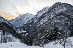 在日落天空,朱利安阿尔卑斯,斯洛文尼亚的田园诗高山多雪的山景 免版税库存图片