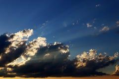 在日落太阳通过黑暗和明亮的云彩发光 免版税图库摄影