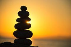 在日落射击的石头平衡 免版税库存照片