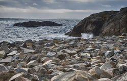 在日落小时,沿着Lofoten海岛的石海滨在挪威 免版税库存照片