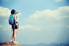 在日落山的妇女远足者饮用水 库存图片
