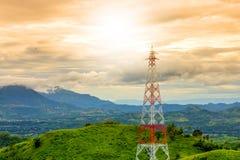 在日落山背景期间的电信塔在rai 免版税图库摄影