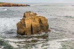 在日落峭壁的鸟岩石地质结构 库存照片