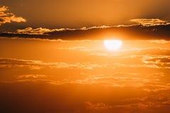 在日落日出天空Cloudscape的明亮的橙色和黄色温暖的颜色太阳 免版税库存照片