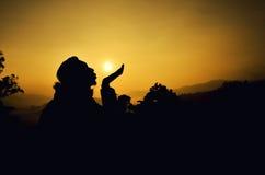 在日落日出期间,供以人员亲吻太阳剪影 库存照片