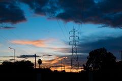 在日落时光的电定向塔剪影 免版税库存图片