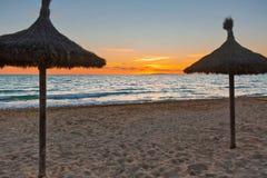 在日落时间的沙滩伞 免版税库存照片