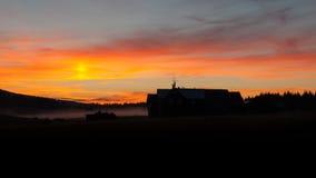 在日落时间的山小屋黑暗的剪影 图库摄影