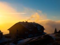 在日落时间的山小屋黑暗的剪影 免版税库存图片