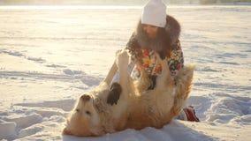 在日落时间,年轻美丽的愉快的女孩使用与在雪的一条猎犬狗在冬天在晴天 库存图片