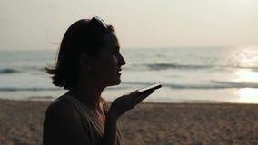 在日落期间的剪影年轻旅游妇女用途电话智能手机音频消息语音识别应用ai  股票录像