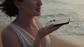 在日落期间的女孩年轻旅游妇女用途电话智能手机音频消息语音识别应用ai在海洋 股票视频