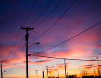 在日落期间的输电线 免版税图库摄影
