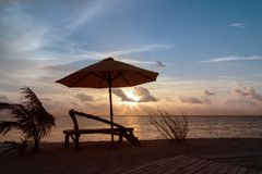 在日落期间的长凳和伞剪影在一个热带地点 免版税库存图片