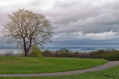 在日落期间的Calton小山在雨前,俯视市爱丁堡和北海,苏格兰,英国 库存图片