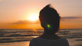 在日落期间,在海滨和神色站立往天际女孩的剪影 股票录像