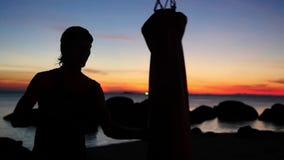 在日落期间,年轻运动人剪影装箱,与吊袋的实践在海滩 慢的行动 股票录像