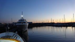 在日落期间,开汽车航行游艇在小游艇船坞 库存图片