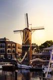 在日落期间,怀有与帆船和一台老风车 库存图片