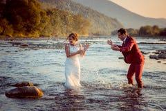 在日落期间,愉快的新婚佳偶夫妇用水使用在河 新郎在新娘飞溅水 库存照片