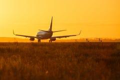 在日落期间,登陆一架大型飞机 库存照片