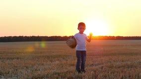 在日落期间,领域的一个孩子穿在他的头的一个草帽 影视素材