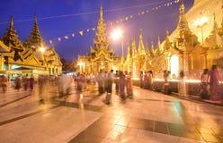 在日落期间, Crowded的献身者&明亮地点燃了Shwedagon塔在晚上 库存图片