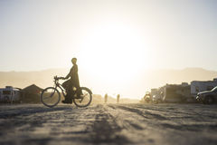 在日落期间的一辆燃烧器骑马自行车在灼烧的人2015年 免版税库存图片
