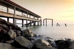 在日落期间的不可思议的片刻与跳船和岩石在海滩 一些弄脏行动由于长的曝光射击 库存图片
