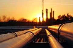 在日落期间的原油精炼厂与管道conection 免版税库存图片