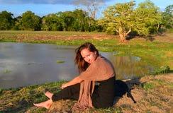 在日落期间的少妇由湖在国家公园 免版税库存图片