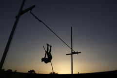 在日落期间的撑竿跳高 免版税库存图片