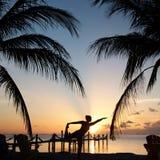 在日落期间的海滩瑜伽 免版税库存照片
