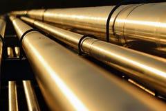 在日落期间的金黄钢管道 免版税库存照片