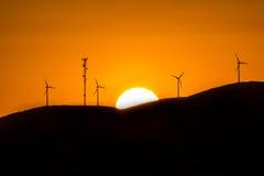 在日落期间的风车在小山 免版税图库摄影