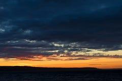 在日落期间的风雨如磐的晚上天空在海岛上 免版税库存图片