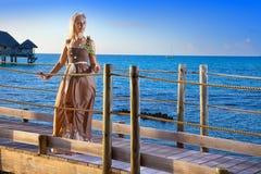 在日落期间,一件长的礼服的年轻美丽的妇女在手上花费与一朵白色玫瑰在海的木路 图库摄影