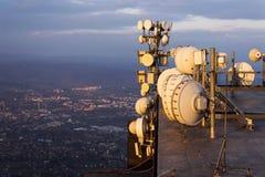 在日落期间,在电信的束发射机和天线耸立 库存照片