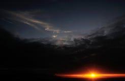 在日落期间,太阳通过一朵黑暗的云彩爬行 库存图片