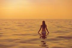 在日落期间,妇女向游泳求助 免版税库存照片