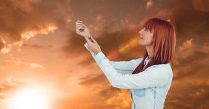 在日落期间,有胳膊的红头发人妇女上升了反对天空 库存照片