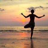 在日落期间,瑜伽妇女执行在海滩的一锻炼 库存照片