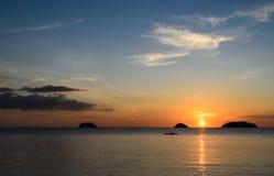 在日落期间,皮艇在海洋现出轮廓 库存照片