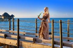在日落期间,美丽的妇女在手上花费与一朵白色玫瑰在海的木路 图库摄影