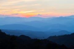 在日落期间,美丽的蓝色山在雾分层堆积 库存图片