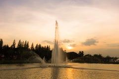在日落树荫背景的喷泉 免版税库存照片