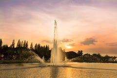 在日落树荫背景的喷泉 图库摄影